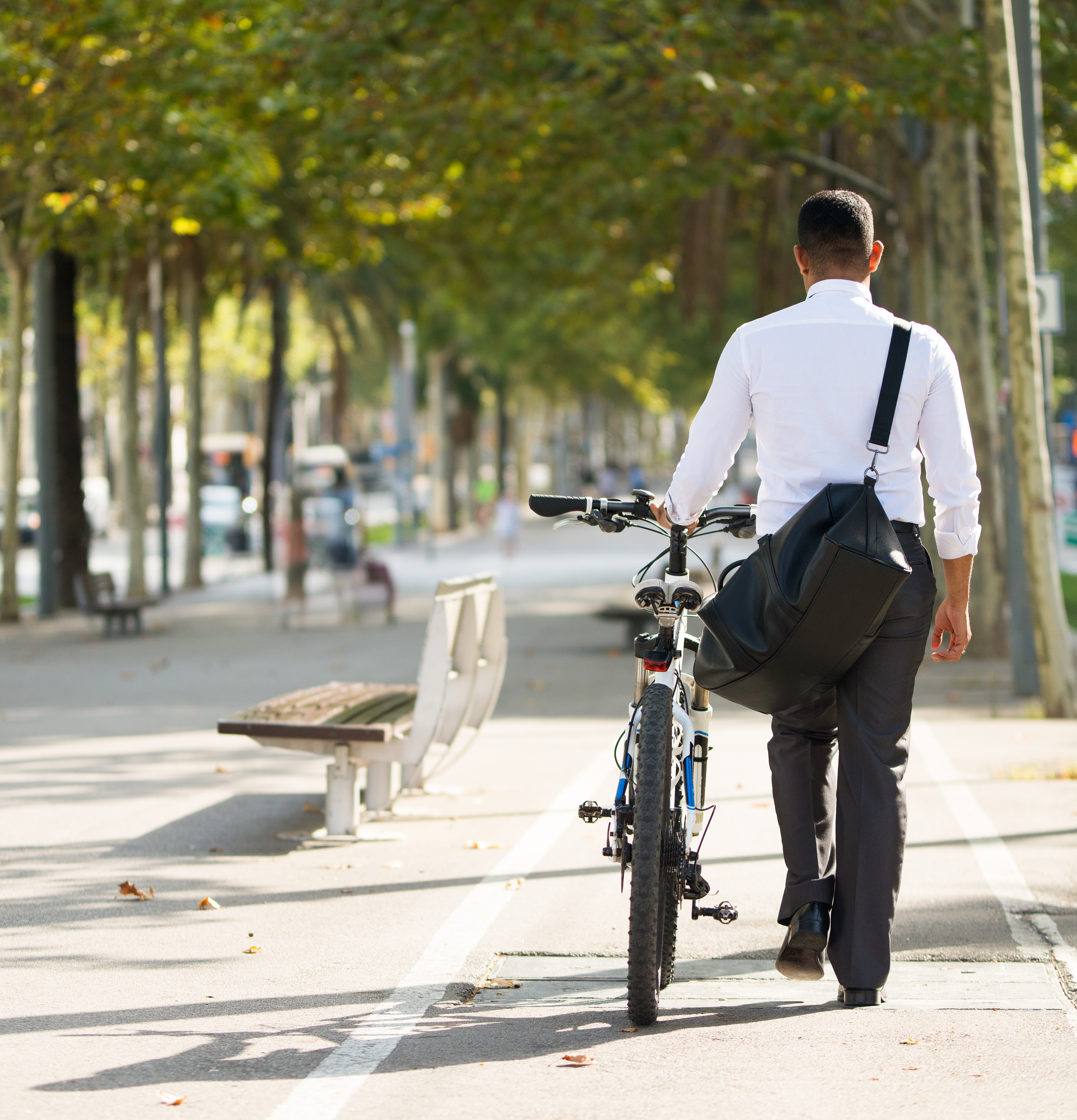 back-view-businessman-walking-with-bike-park square