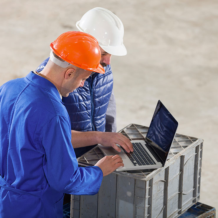 Two people wearing hard hats looking at a laptop