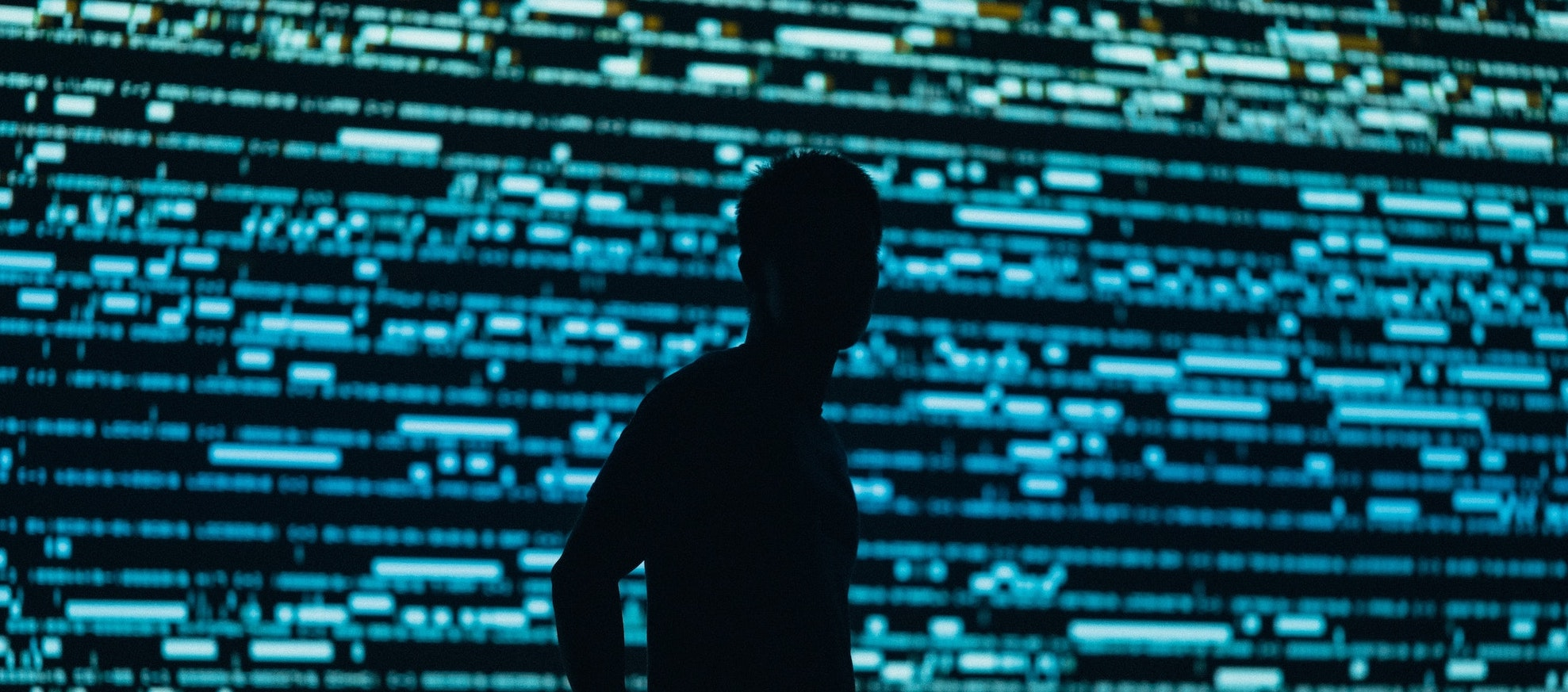 Man in front of screen of code